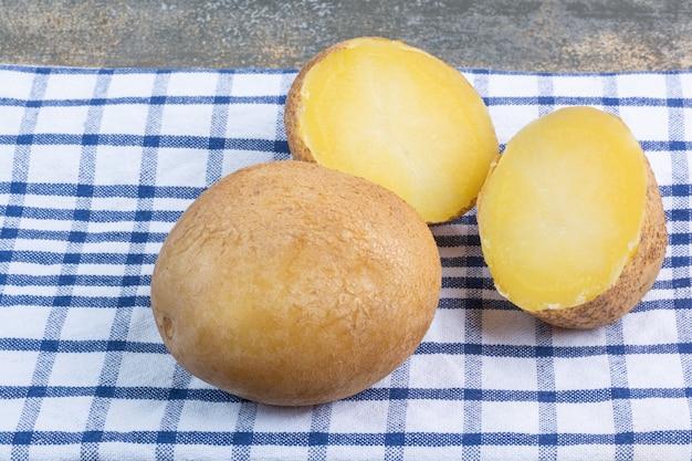 Pommes de terre bouillies entières et tranchées sur une serviette, sur le marbre.