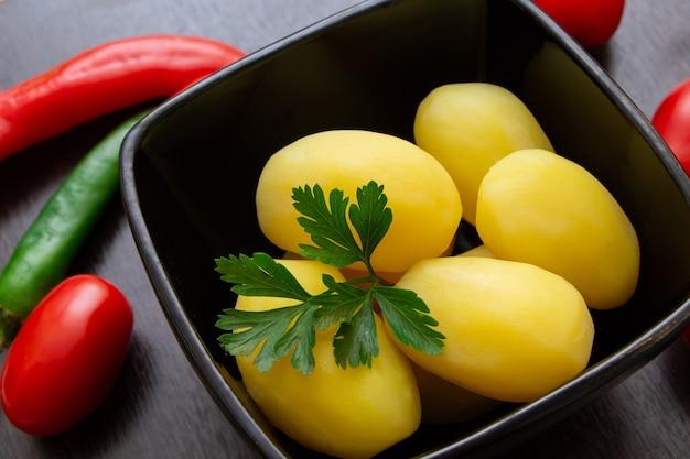 Pommes de terre bouillies avec piments et tomates sur fond sombre