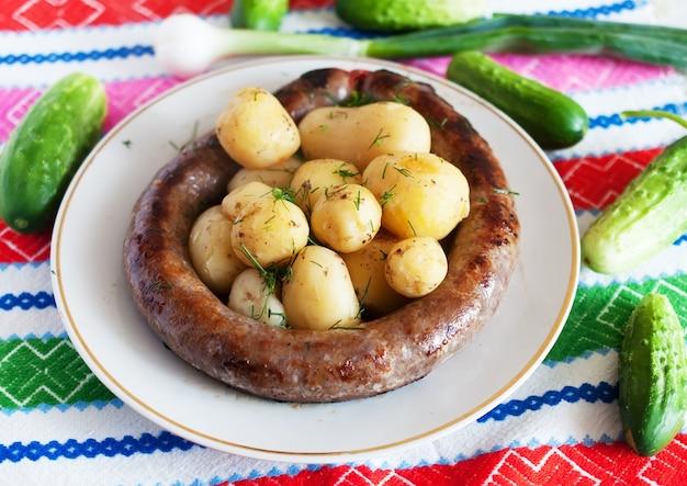 Pommes de terre bouillies avec saucisse ukrainienne et légumes verts.