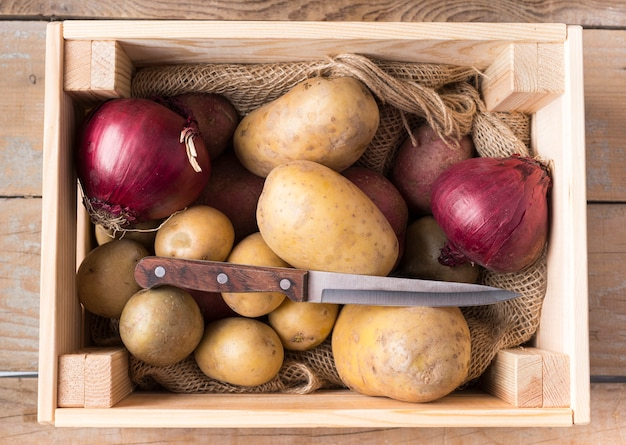 Pommes de terre crues dans une boîte en bois avec couteau