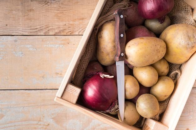 Pommes de terre crues dans une boîte en bois avec espace copie