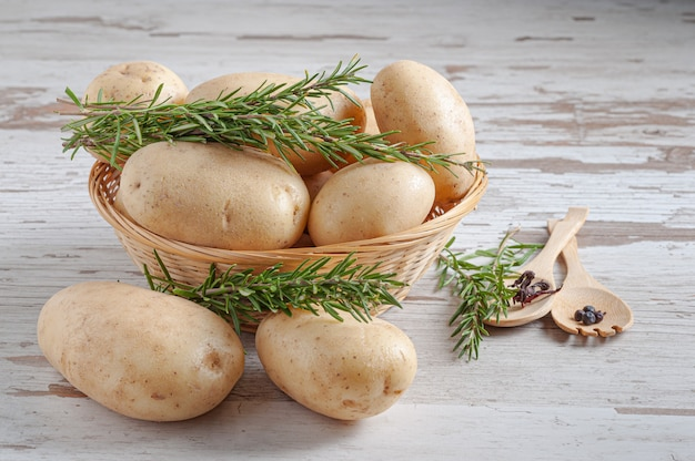 Pommes de terre crues dans un panier en osier tressé avec des feuilles de romarin naturel sur une surface de table rustique en bois
