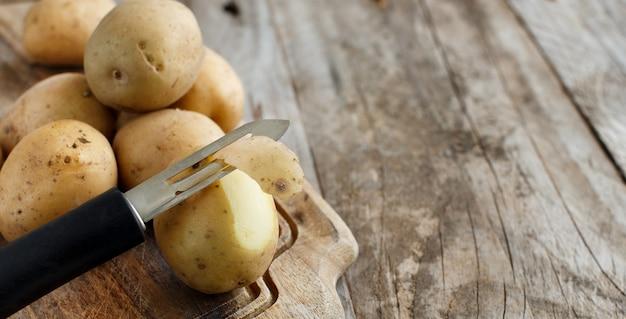 Pommes de terre crues avec un éplucheur de légumes close up