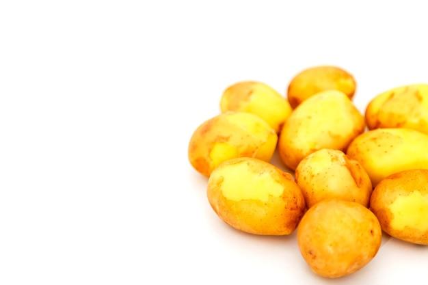 Pommes de terre crues sur fond blanc. pommes de terre fraîches isolées. récolte précoce. légumes lavés. mise au point sélective. concept de compétence culinaire. place pour une inscription ou un logo