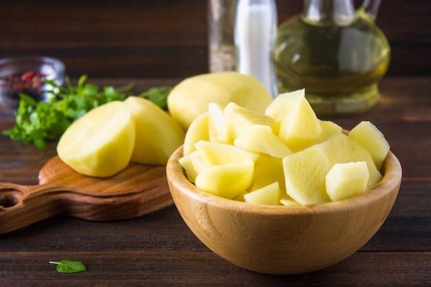 Pommes de terre crues pelées et tranchées sur une vieille table en bois patinée.