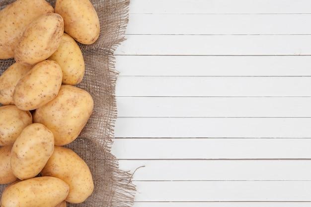 Pommes de terre crues avec toile de jute sur blanc