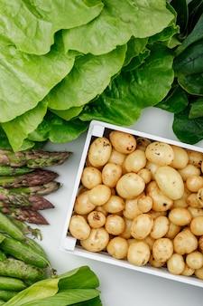 Pommes de terre dans une boîte en bois avec des gousses vertes, épinards, oseille, laitue, asperges à plat sur un mur blanc
