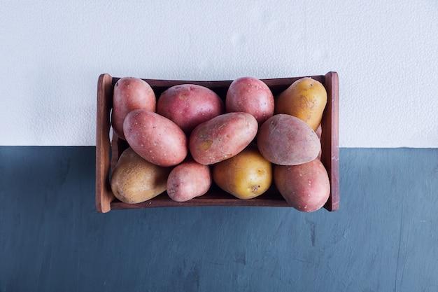 Pommes de terre dans un panier en bois.