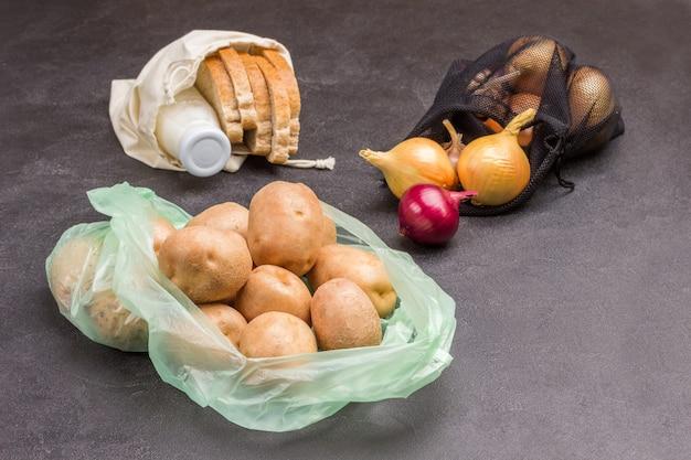 Pommes de terre dans un sac en plastique avec du pain et du lait dans un sac en lin
