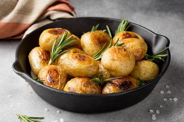 Pommes de terre entières frites (cuites au four) avec du romarin et du sel dans une poêle à frire, croûte vermeille, aliments appétissants