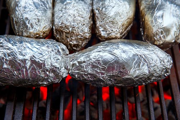 Pommes de terre entières grillées avec du papier d'aluminium