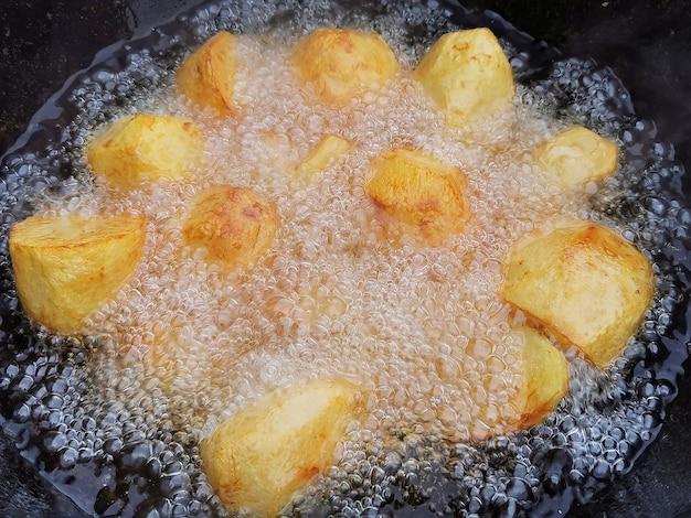 Les pommes de terre entières sont frites dans un chaudron noir profond avec beaucoup d'huile. régime de style de vie malsain, fast food gras et gras