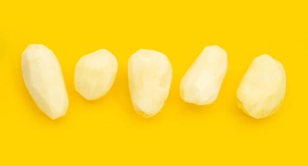 Pommes de terre épluchées crues sur fond blanc