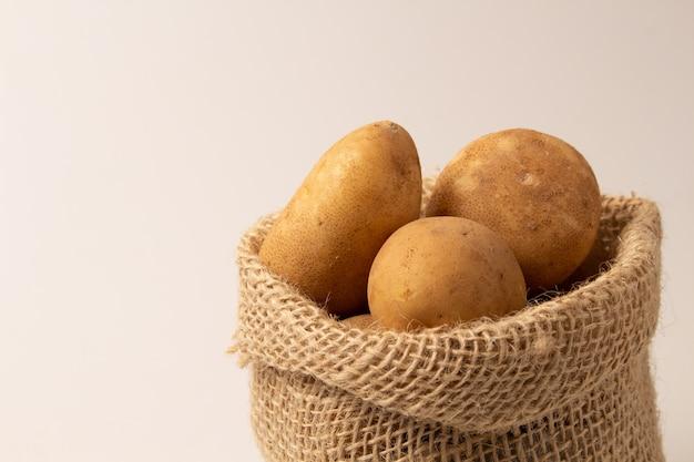 Pommes de terre fraîches et crues dans un sac rustique isolé sur blanc