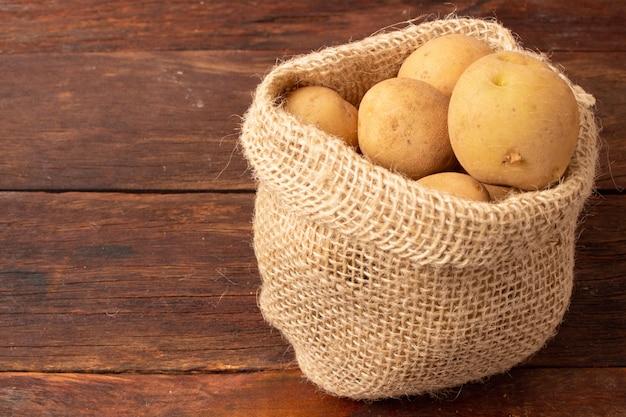 Pommes de terre fraîches et crues dans un sac rustique sur une table en bois