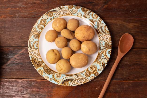 Pommes de terre fraîches et crues empilées dans un plat rond sur une table en bois