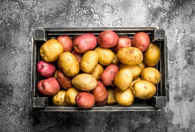 Pommes de terre fraîches dans une boîte sur table rustique.