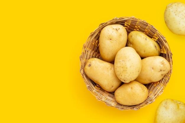 Pommes de terre fraîches dans un panier en bambou sur fond jaune.