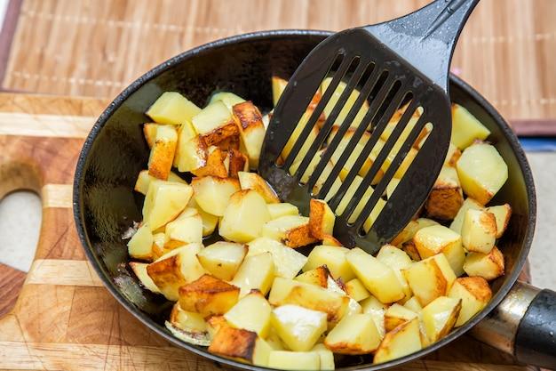 Pommes de terre fraîches frites dans une poêle avec de l'huile et une tige d'agitation se bouchent