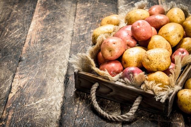 Pommes de terre fraîches sur plateau en bois sur table en bois.