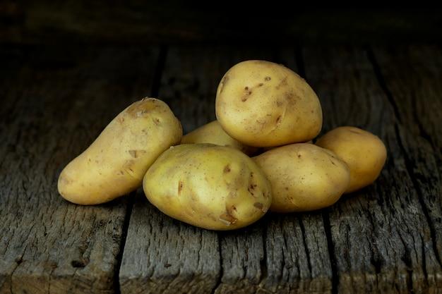 Pommes de terre fraîches sur une vieille table en bois
