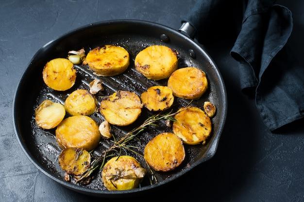 Pommes de terre frites à l'ail et au romarin dans une poêle à frire.