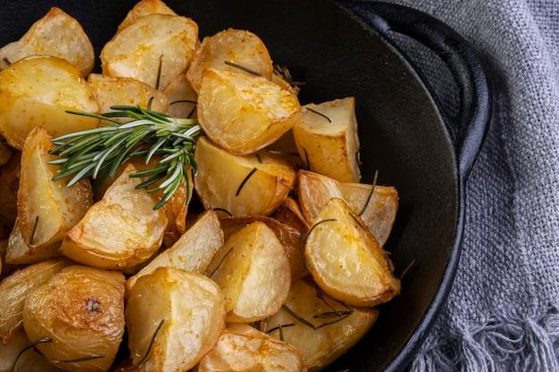 Pommes de terre frites au four avec romarin, gros sel, huile d'olive et paprika épicé dans une poêle en fer.