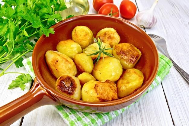 Pommes de terre frites au romarin dans une casserole en céramique sur une serviette, ail, persil, huile végétale, tomates sur fond de planches de bois