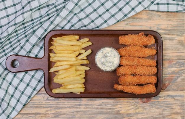 Pommes de terre frites et bâtonnets de poulet avec sauce blanche.