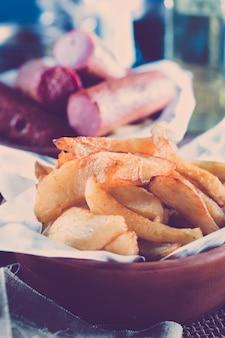 Pommes de terre frites dans un bol, avec des saucisses grillées et de la bière en arrière-plan. dans le filtre de style instagram.