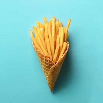 Pommes de terre frites dans des cônes de gaufres sur fond bleu. frites salées chaudes avec sauce tomate. restauration rapide, malbouffe, concept de régime.