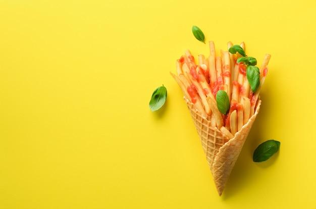 Pommes de terre frites dans des cônes de gaufres sur fond jaune. frites salées chaudes avec sauce, feuilles de basilic. restauration rapide, malbouffe, concept de régime.