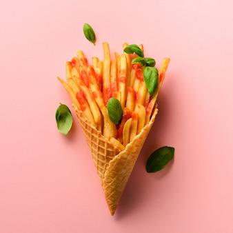 Pommes de terre frites dans des cônes de gaufres sur fond rose. frites salées chaudes avec sauce, feuilles de basilic. restauration rapide, malbouffe, concept de régime.