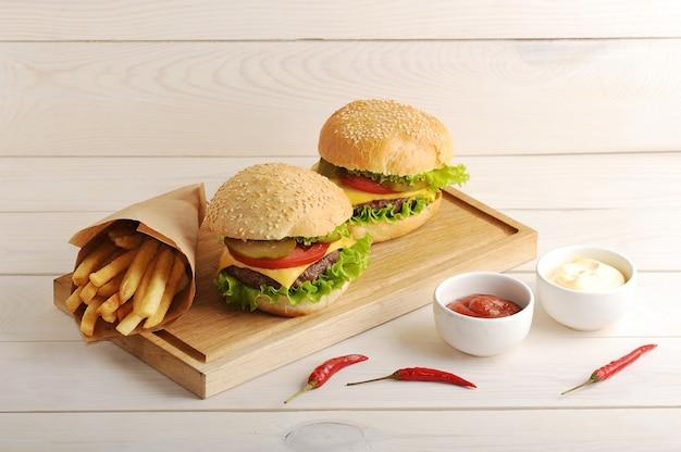Pommes de terre frites dans un sac en papier, sauce au fromage, ketchup et deux hamburger