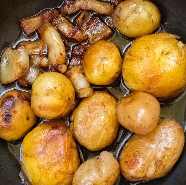Pommes de terre frites dorées au saindoux dans une poêle, style rustique. mise à plat. fond, texture