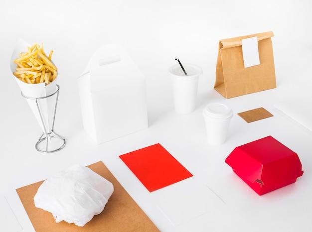 Pommes de terre frites avec emballages de nourriture et gobelet sur fond blanc