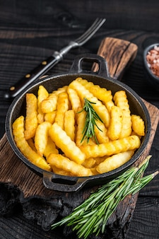 Pommes de terre frites frites dans une poêle. fond en bois noir. vue de dessus.