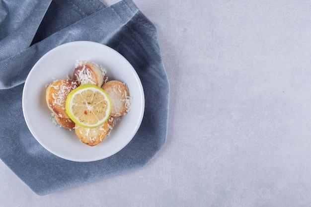 Pommes de terre frites garnies de fromage râpé et de citron sur une assiette blanche.