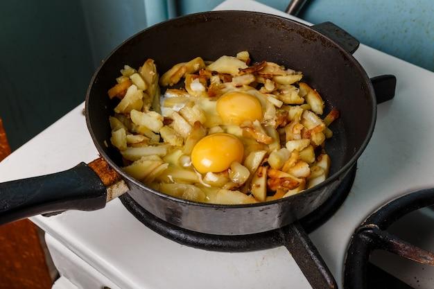 Pommes de terre frites avec oeuf dans une poêle à frire, célibataire