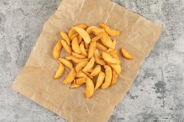 Pommes de terre frites sur papier sulfurisé sur fond de pierre.