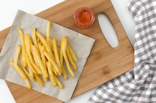 Pommes de terre frites sur planche à découper avec sauce vue de dessus.