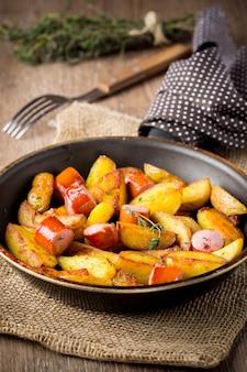 Pommes de terre frites avec des saucisses dans une poêle à frire, tatsy, fait maison, nourriture simple, style rustique