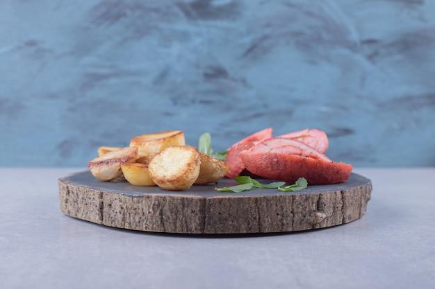 Pommes de terre frites et saucisses sur morceau de bois.