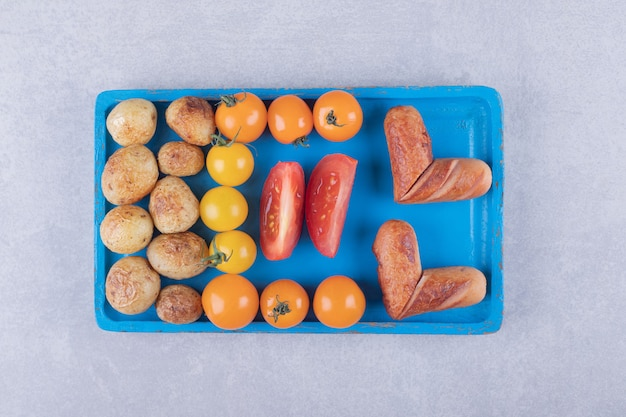 Pommes de terre frites et saucisses sur plaque bleue.