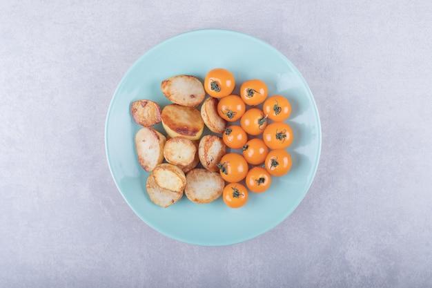 Pommes de terre frites et tomates sur plaque bleue.