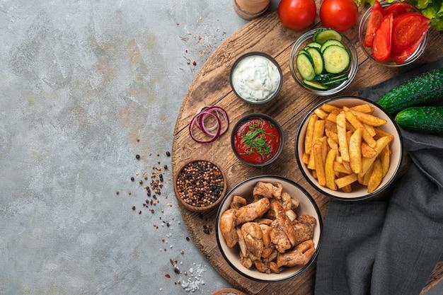 Pommes de terre frites, viande de poulet et légumes sur une planche de bois sur un mur gris. vue de dessus, espace pour le carottage.
