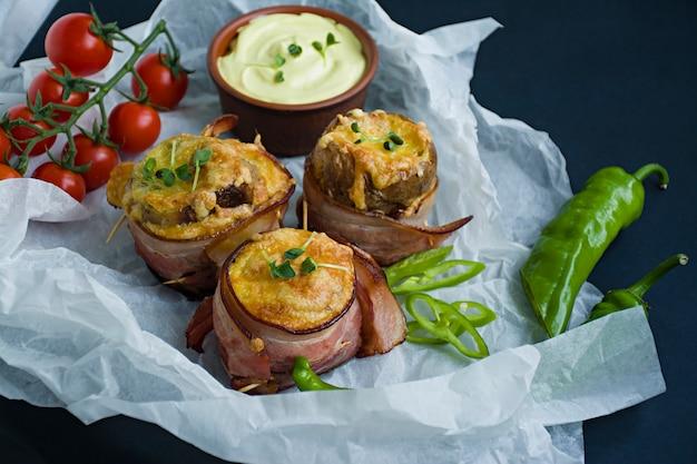 Pommes de terre nouvelles cuites au four enveloppées dans du bacon, sur du fromage, du micro-vert, de la sauce et des légumes frais.