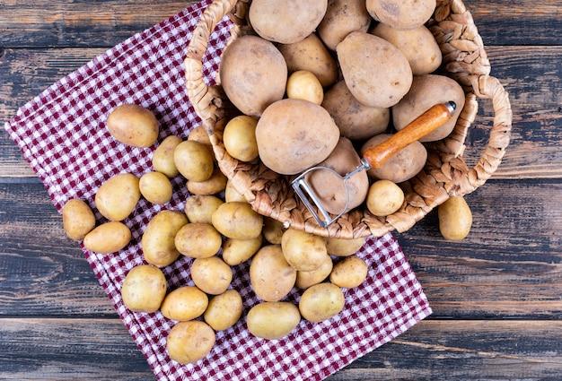 Pommes de terre pelées avec éplucheur de pommes de terre dans un panier et sur un tissu de pique-nique, sur une table en bois gris