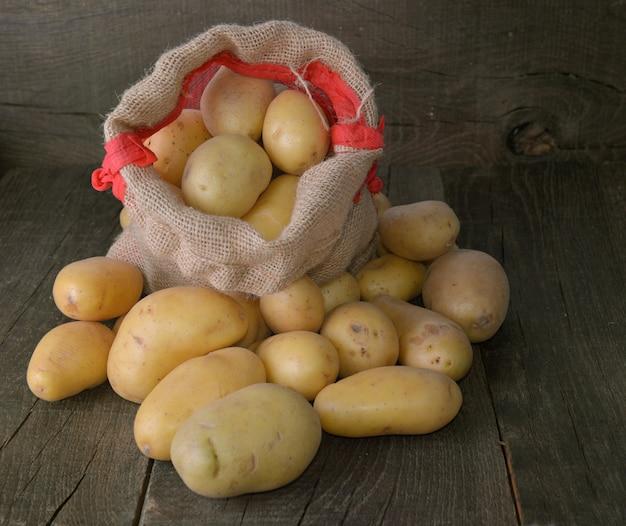 Pommes de terre sur un petit sac parmi d'autres pommes de terre sur fond en bois rustique