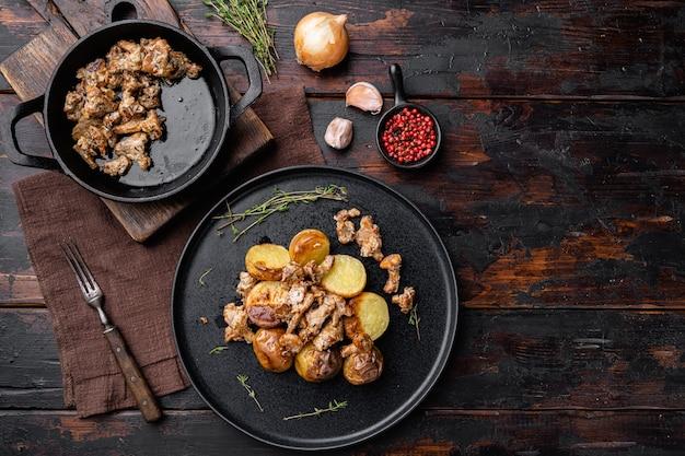 Pommes de terre rôties aux girolles et oignons, sur fond de table en bois sombre, vue de dessus à plat, avec espace de copie pour le texte